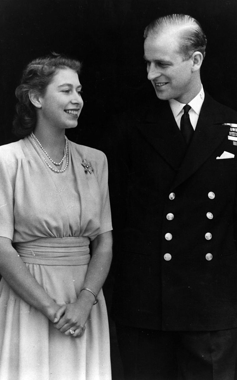 Princess Elizabeth and Philip Mountbatten, Duke of Edinburgh, on the occasion of their engagement in 1947 at Buckingham Palace - Credit: Fox Photos/Getty Images