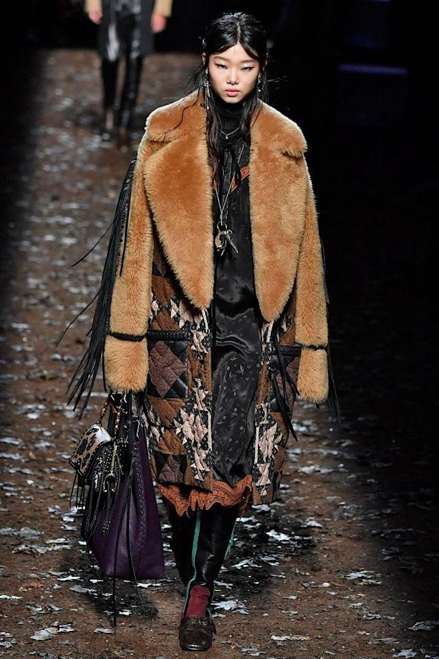 <p>Model wears a teddy-bear shearling and quilt coat over a black bandana-print dress at the Coach Fall 2018 show. (Photo: Getty) </p>