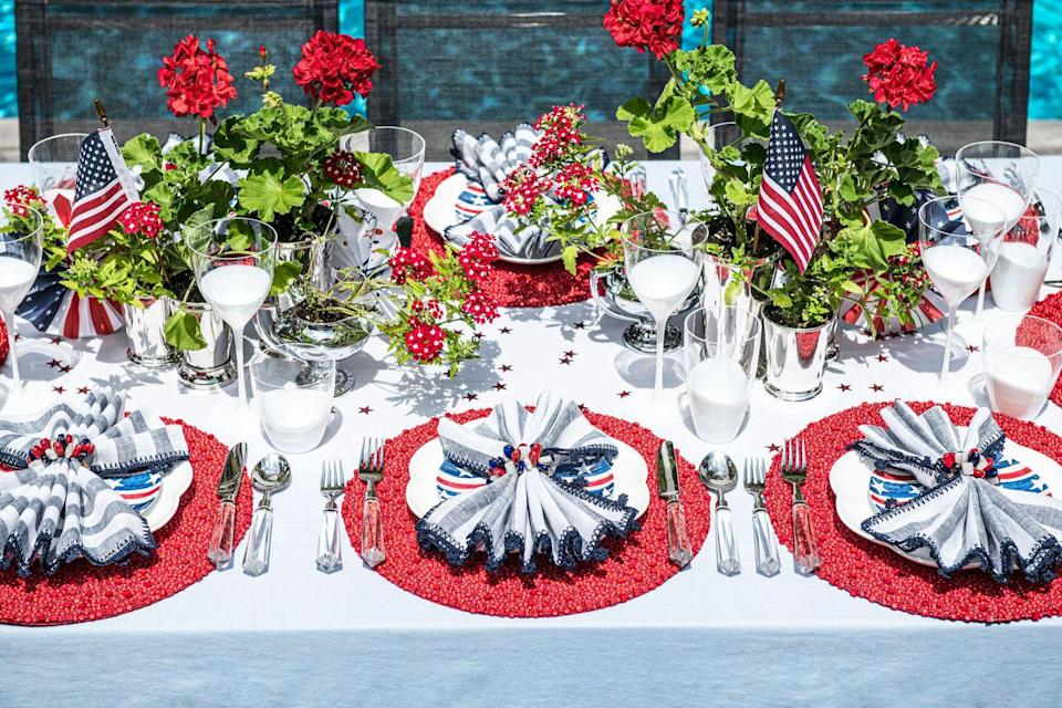 """<p><strong>How do you find the balance between festive and kitschy when it comes to decorating for a holiday?</strong></p><p>I'm a big believer that there are some holidays where tables can be kitschy and the Fourth of July is one of them! So often summer celebrations involve the whole family, and I want to make sure everyone enjoys the setting—kids included. To keep the evening festive, I love incorporating elements such as silver mint julep cups to hold flowers or making sure items such as the placemats or napkin rings feature intricate detailing that adds interest and excitement. This year, I'll be spreading some star confetti on the table that I'm sure the kids are going to love! </p><p><strong>What are a few of your favorite florals to decorate with for the Fourth? </strong></p><p>I love using flowers that add a welcoming element to the table. This year's flowers will be red geraniums and verbena planted in silver mint julep cups. I feel combining these two strikes the perfect balance between a glamorous and casual get-together.</p><p><em>Shop the Look: <a href=""""https://kimseybert.com/products/linea-napkin-in-white-navy?variant=31806330273853"""" rel=""""nofollow noopener"""" target=""""_blank"""" data-ylk=""""slk:Linen Napkins"""" class=""""link rapid-noclick-resp"""">Linen Napkins</a>, <a href=""""https://kimseybert.com/products/poppy-napkin-ring-in-red-white-blue?variant=31806334206013"""" rel=""""nofollow noopener"""" target=""""_blank"""" data-ylk=""""slk:Napkin Rings"""" class=""""link rapid-noclick-resp"""">Napkin Rings</a>, and <a href=""""https://kimseybert.com/products/bianco-placemat-in-coral-set-of-4?variant=33018396934205"""" rel=""""nofollow noopener"""" target=""""_blank"""" data-ylk=""""slk:Placemats"""" class=""""link rapid-noclick-resp"""">Placemats</a>, Kim Seybert</em></p>"""