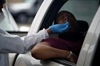 A health care worker administers a COVID-19 test at United Memorial Medical Center testing site in Houston, Texas -- now only the third state to register more than 10,000 virus cases in a 24-hour period