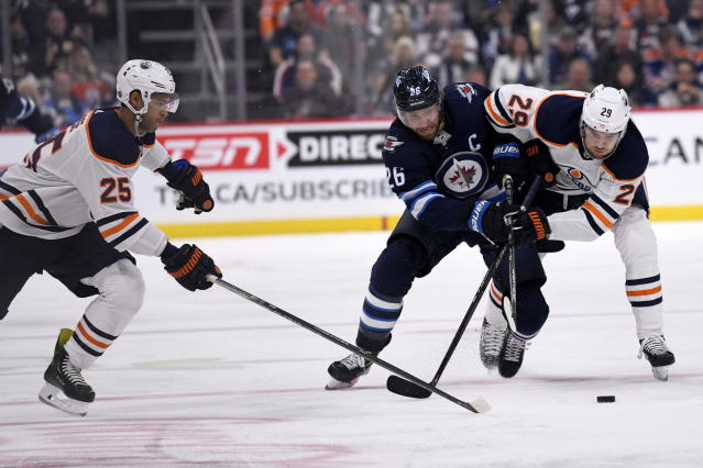 Edmonton Oilers' Darnell Nurse (25) scoops up the puck as Winnipeg Jets' Blake Wheeler (26) is checked by Leon Draisaitl (29) during second-period NHL hockey game action in Winnipeg, Manitoba, Sunday, Oct. 20, 2019. (Fred Greenslade/The Canadian Press via AP)