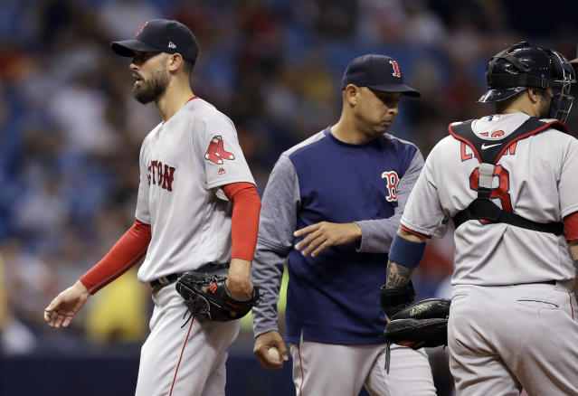 Boston Red Sox manager Alex Cora, center, takes starting pitcher Rick Porcello, left, out of the baseball game during the fourth inning against the Tampa Bay Rays on Thursday, May 24, 2018, in St. Petersburg, Fla. At right is catcher Sandy Leon. (AP Photo/Chris O'Meara)