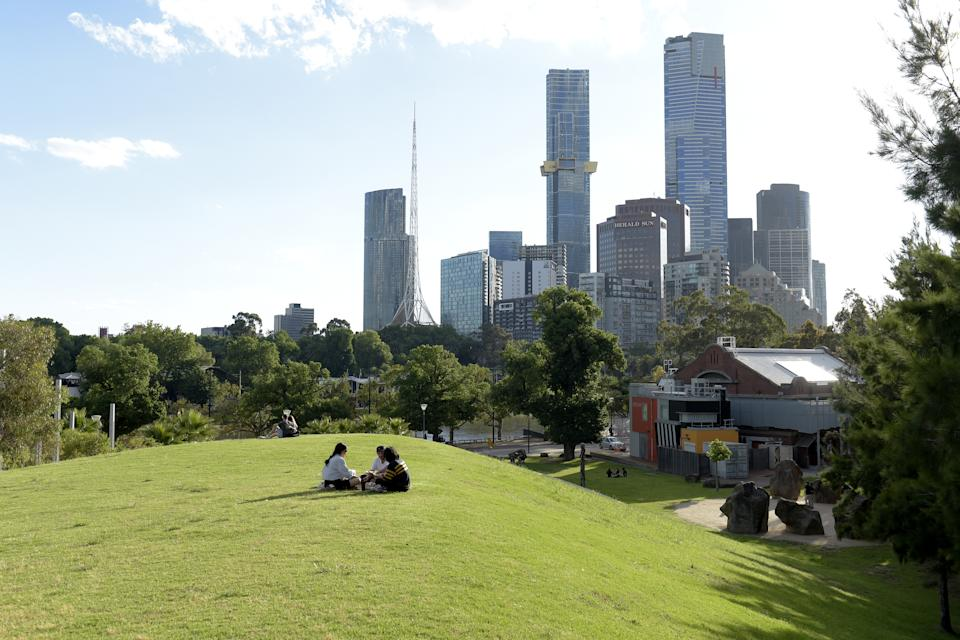 Pictured are people sitting on top of a grassy hill overlooking Melbourne's CBD.