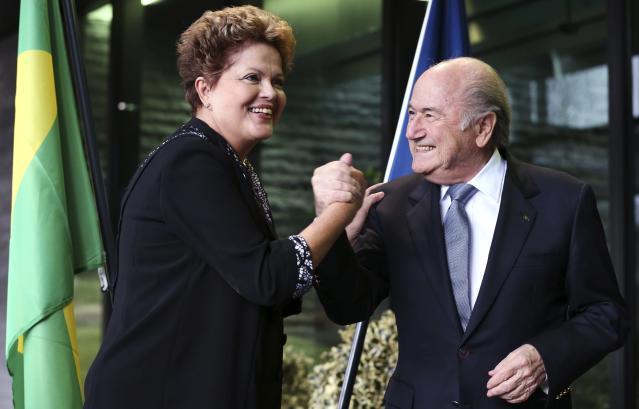 Brazil's President Dilma Rousseff (L) greets FIFA President Sepp Blatter during a visit at the FIFA headquarters in Zurich January 23, 2014. The 2014 World Cup final tournament will be held in Brazil from June 12 through July 13. REUTERS/Thomas Hodel (SWITZERLAND - Tags: SPORT SOCCER WORLD CUP POLITICS)