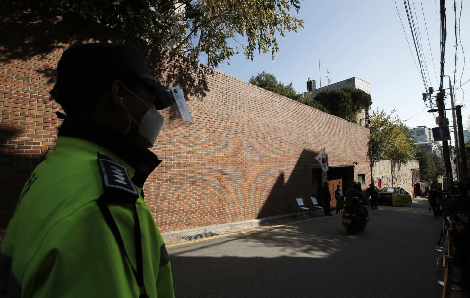 A South Korean police officer stands outside a residence of former President Lee Myung-bak in Seoul, South Korea, Thursday, Oct. 29, 2020. South Korea's top court upheld a 17-year sentence imposed on former President Lee Myung-bak for a range of corruption crimes in a final ruling Thursday that will send him back to prison. (AP Photo/Lee Jin-man)