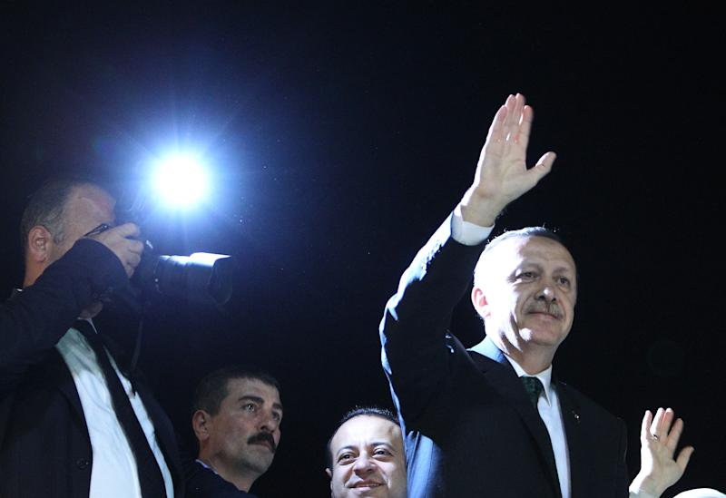 Turkish Prime Minister Recep Tayyip Erdogan, right, waves to the crowd upon his arrival at the Ataturk Airport of Istanbul early Friday, June 7, 2013. Erdogan took a combative stance on his closely watched return to the country early Friday, telling supporters who thronged to greet him that the protests that have swept the country must come to an end. (AP Photo/Thanassis Stavrakis)