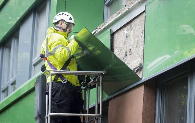 A worker in a hi-vis jacket and a white hard hat removes a green panel from a building