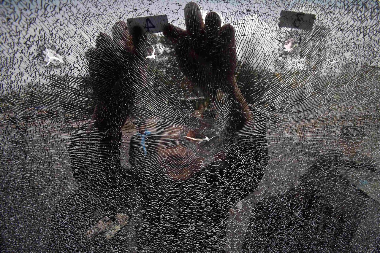 A police officer inspects the damaged windshield of a police bus after clashes between police and rubber farmers in Bangsaphan, Prachuap Khiri Khan September 6, 2013. Thailand faced pressure on Friday to end a two-week protest by rubber farmers after violent overnight clashes between riot police and a group of protesters who hurled rocks and bottles filled with an acidic liquid. Police fired tear gas to disperse the group in Prachuap Khiri Khan province on a main road from Bangkok to the southern beach resort region of Phuket. At least 21 policemen were injured, authorities said. Tens of thousands of farmers in the country's main southern rubber-producing region are demanding greater state support after a slowdown in demand from China and concerns over global economic growth sent prices tumbling to multi-year lows in mid-2012. REUTERS/Athit Perawongmetha (THAILAND - Tags: BUSINESS CIVIL UNREST POLITICS AGRICULTURE TPX IMAGES OF THE DAY)