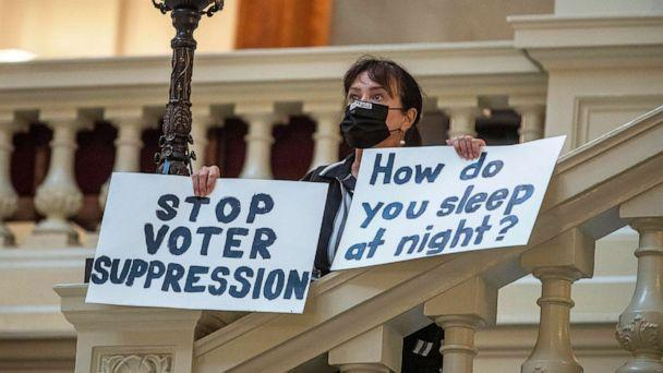 PHOTO: Ann White of Roswell holds protest signs on the North Wing stairs of the Georgia State Capitol building on day 38 of the legislative session in Atlanta, March 25, 2021.  (Alyssa Pointer/Atlanta Journal-Constitution via AP)