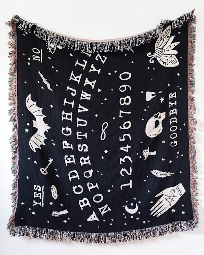 """Get wrapped up in the supernatural world with this Ouija-themed <a href=""""https://www.architecturaldigest.com/gallery/fall-throw-blankets-we-want?mbid=synd_yahoo_rss"""" rel=""""nofollow noopener"""" target=""""_blank"""" data-ylk=""""slk:throw blanket"""" class=""""link rapid-noclick-resp"""">throw blanket</a>. $79, Frankie Print Co. <a href=""""https://frankieprintco.com/products/ouija-woven-throw-blanket"""" rel=""""nofollow noopener"""" target=""""_blank"""" data-ylk=""""slk:Get it now!"""" class=""""link rapid-noclick-resp"""">Get it now!</a>"""