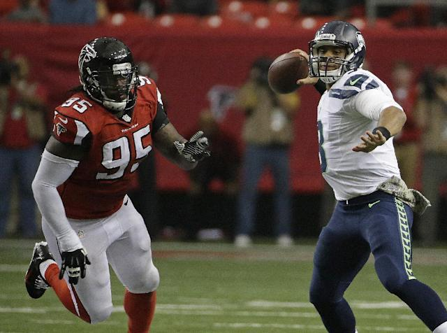 Seattle Seahawks quarterback Russell Wilson (3) works as Atlanta Falcons defensive tackle Jonathan Babineaux (95) pursues during the first half of an NFL football game, Sunday, Nov. 10, 2013, in Atlanta. (AP Photo/David Goldman)