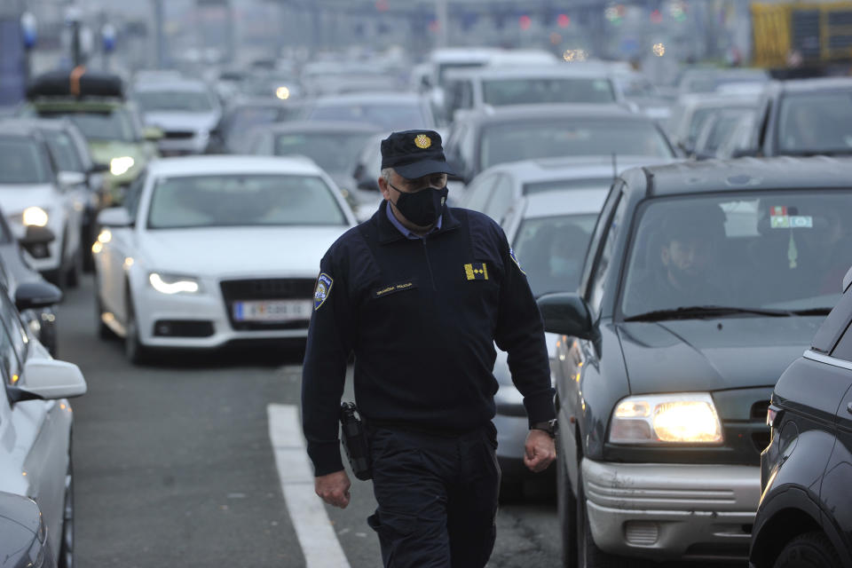 A Croatian border police officer walks between vehicles as motorists wait to cross the Croatian border from Slovenia, at Bregana border crossing, western Croatia, Saturday, Dec. 19, 2020. Balkan citizens going home from Western Europe for holidays have created huge traffic jams at border crossings despite coronavirus restrictions meant to discourage travel for Christmas and the New Year. Huge lines of cars have formed on the borders between Slovenia and Croatia as well as Hungary and Serbia as thousands of people waited for hours Saturday to cross. (AP Photo)