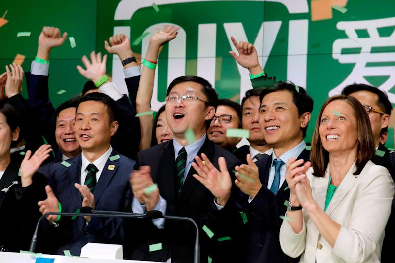 iQIYI Founder & CEO Yu Gong, center, and Robin Li, second from right, co-founder of the search engine Baidu, ring the Nasdaq MarketSite opening bell, during iQIYI IPO listing ceremonies, in New York's Times Square, Thursday, March 29, 2018. Nasdaq CEO Adena Friedman is at right. (AP Photo/Richard Drew)