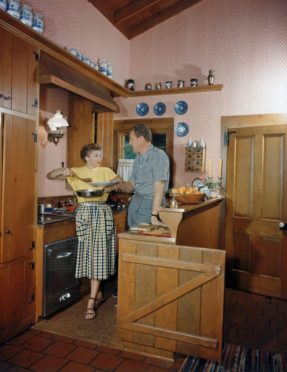 <p>Between the wooden accents and the ginger jars, actress Esther William's kitchen is a slice of Americana. Here, she cooks dinner with her husband, singer Ben Gage, in 1950. </p>