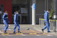 Police forensic staff walk outside a supermarket in Auckland, New Zealand, Saturday, Sept. 4, 2021. New Zealand authorities say they shot and killed a violent extremist, Friday Sept. 3, after he entered a supermarket and stabbed and injured six shoppers. Prime Minister Jacinda Ardern described Friday's incident as a terror attack. (AP Photo/Brett Phibbs)