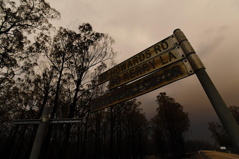 A scorched street sign is seen following a bushfire in Bruthen South, Victoria, Saturday, January 4, 2019. Twenty-two people are dead, 21 more are missing and more than 1500 homes have been destroyed as fires burned through over six-million hectares of land. (AAP Image/James Ross)