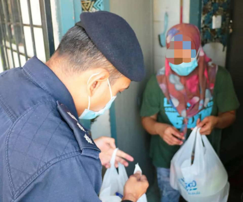 Petaling Jaya police deliver food aid to a housewife who was caught shoplifting food for her children, January 21, 2021. — Picture from Facebook/Polis Daerah Petaling Jaya