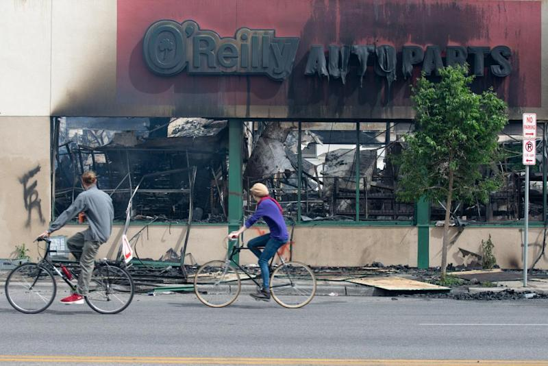 Cyclists ride past the burned out O'Reilly Auto Parts store in Minneapolis.