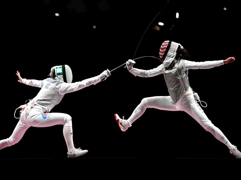Two fencers lunge at the Tokyo Olympics.