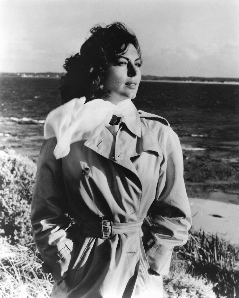 <p>The American actress looks away from the camera on the set of <em>On the Beach</em>, the film directed by Stanley Kramer. She wears a chiffon scarf and classic trench coat. </p>