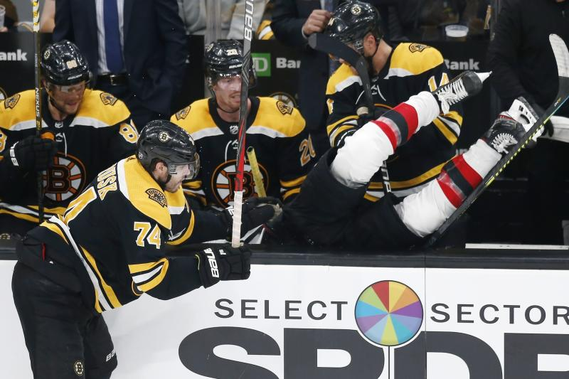 Boston Bruins' Jake DeBrusk (74) checks New Jersey Devils' Kevin Rooney into the Bruins' bench during the third period of an NHL hockey game in Boston, Saturday, Oct. 12, 2019. (AP Photo/Michael Dwyer)