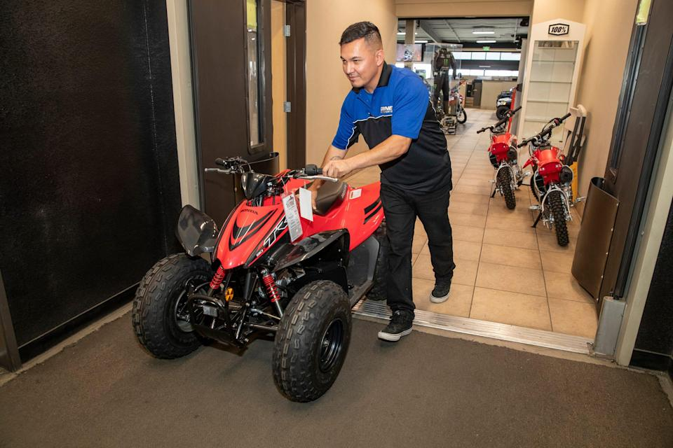 Coyne Powersports employee Armando Berdusco pushes a newly purchased all-terrain vehicle from the showroom to the shop in preparation for delivery to a customer at the store in El Centro, Calif., on July 8, 2021. Berdusco of El Centro has worked at the growing local business for the past four years.