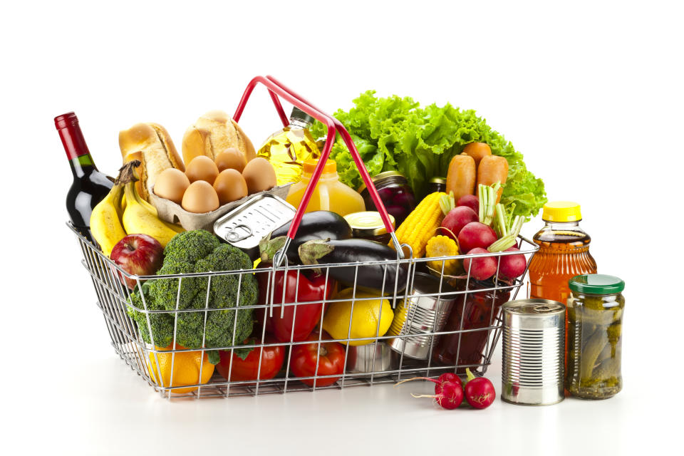 Side view of a wire shopping basket filled with all sort of food including fresh vegetables, fruits, canned food, fruit juice and dairy products.  Some canned food is outside the basket at the right side. Colors are very vibrant and saturated with greens, yellows and reds as predominant colors. The basket is isolated on white background and produces a soft shadow. Studio shot taken with DSRL Canon EOS 5D Mk II
