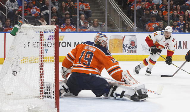 Calgary Flames' Mikael Backlund (11) scores on Edmonton Oilers goalie Mikko Koskinen (19) during the third period of an NHL hockey game in Edmonton, Alberta, Saturday, Jan. 19, 2019. (Jason Franson/The Canadian Press via AP)