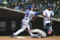 Chicago Cubs shortstop Javier Baez throws to first base after forcing out Atlanta Braves' Guillermo Heredia at second base during the seventh inning of a baseball game Saturday, April 17, 2021, in Chicago. (AP Photo/Paul Beaty)