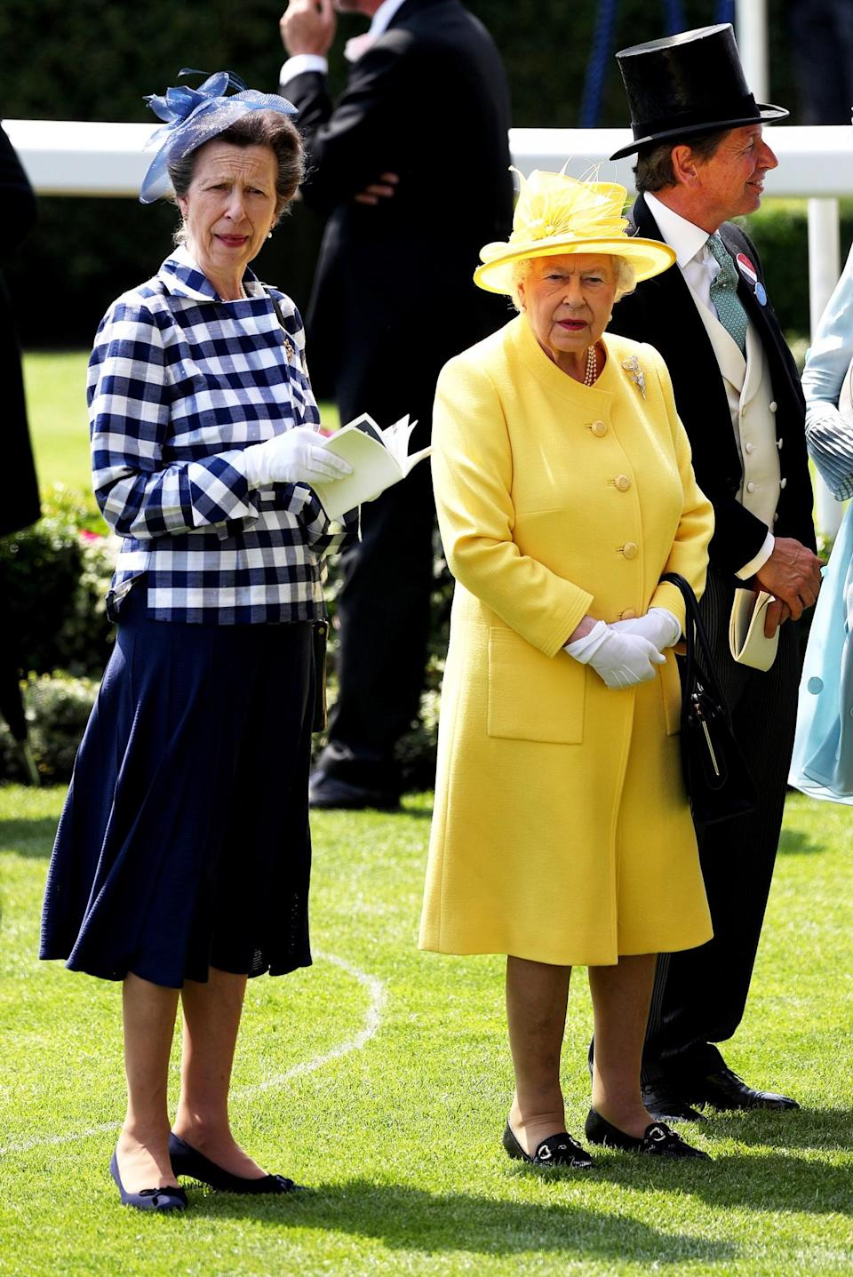<p>For day two of Royal Ascot, the Queen worked a canary yellow ensemble, while her daughter Princess Anne paired a gingham jacket with white gloves and a navy blue skirt. <br><em>[Photo: Getty]</em> </p>