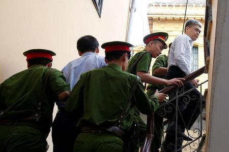 Former Petro Vietnam (PVN) chairman Nguyen Xuan Son (R) is escorted by police to the court for the verdict session in Hanoi, Vietnam September 29, 2017. REUTERS/Kham