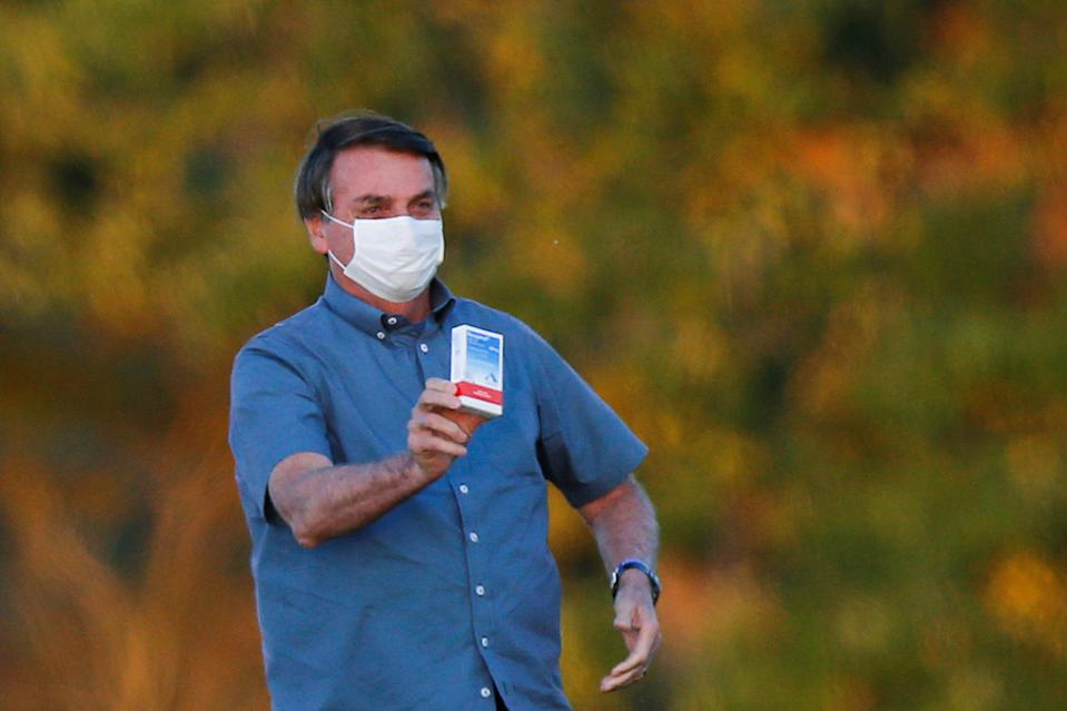 Brazil's President Jair Bolsonaro holds a box of chloroquine outside of the Alvorada Palace, amid the coronavirus disease (COVID-19) outbreak in Brasilia, Brazil, July 23, 2020.REUTERS/Adriano Machado     TPX IMAGES OF THE DAY