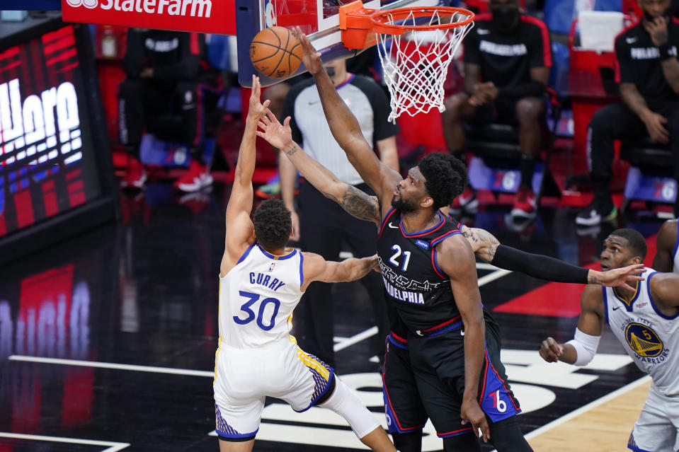 Philadelphia 76ers' Joel Embiid, right, blocks a shot by Golden State Warriors' Stephen Curry during the second half of an NBA basketball game, Monday, April 19, 2021, in Philadelphia. (AP Photo/Matt Slocum)