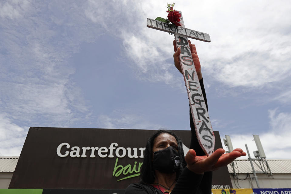 "Holding a cross covered with the Portuguese message ""Black Lives Matter,"" a person demonstrates against the murder of Black man João Alberto Silveira Freitas, which occurred the night before at a different Carrefour supermarket, on Brazil's National Black Consciousness Day in Brasilia, Brazil, Friday, Nov. 20, 2020. Freitas died after being beaten by supermarket security guards in the southern Brazilian city of Porto Alegre, sparking outrage as videos of the incident circulated on social media. (AP Photo/Eraldo Peres)"