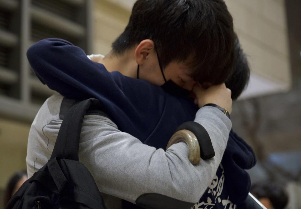 A relative and a friend of one of the 47 pro-democracy activists hug each other outside a court in Hong Kong Thursday, March 4, 2021. A Hong Kong court on Thursday remanded all 47 pro-democracy activists charged under a Beijing-imposed national security law in custody, ending a four-day marathon court hearing. (AP Photo/Vincent Yu)