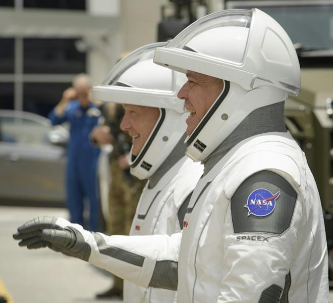 NASA astronauts Douglas Hurley, left, and Robert Behnken, wearing SpaceX spacesuits, are seen as they depart the Neil A. Armstrong Operations and Checkout Building to board the SpaceX Crew Dragon spacecraft -- the mission was eventually scrubbed