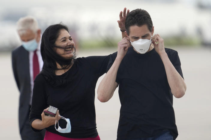 Michael Kovrig, centre right, puts on a facemask as his wife Vina Nadjibulla, center left, walks with him after his arrival at Pearson International Airport in Toronto, Saturday, Sept. 25, 2021. China, the U.S. and Canada completed a high-stakes prisoner swap Saturday with joyous homecomings for Kovrig and Michael Spavor, two Canadians held by China and for an executive of Chinese global communications giant Huawei Technologies charged with fraud. (Frank Gunn /The Canadian Press via AP)
