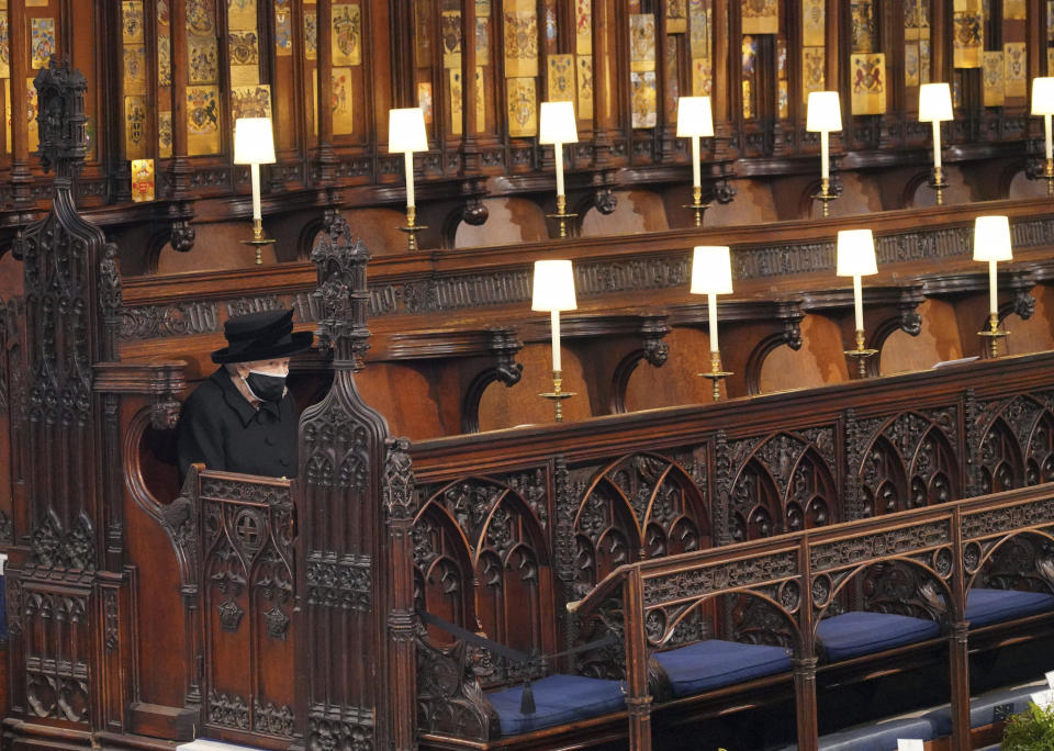 Britain's Queen Elizabeth II sits alone in St. George's Chapel during the funeral of Prince Philip at Windsor Castle, Windsor, England, Saturday April 17, 2021.