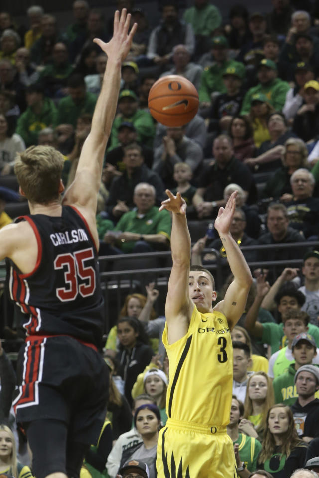 Oregon's Payton Pritchard, right, shoots a 3-pointer over Utah's Branden Carlson during the first half of an NCAA college basketball game in Eugene, Ore., Sunday, Feb. 16, 2020. (AP Photo/Chris Pietsch)
