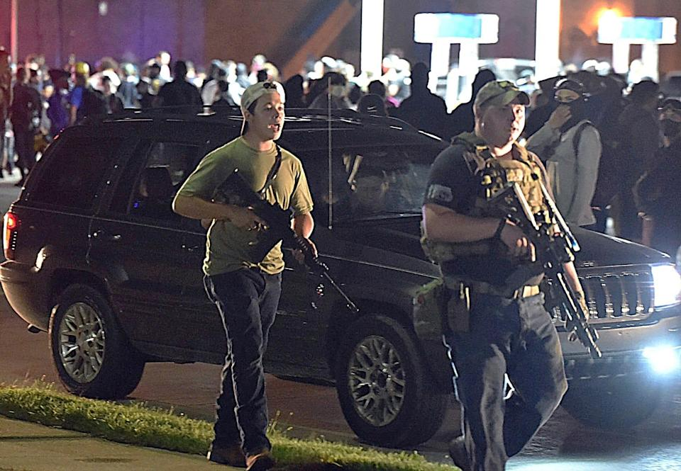 Kyle Rittenhouse, left, and other armed men claimed to be protecting property owners from arson and theft during protests Aug. 25, 2020, in Kenosha, Wis.