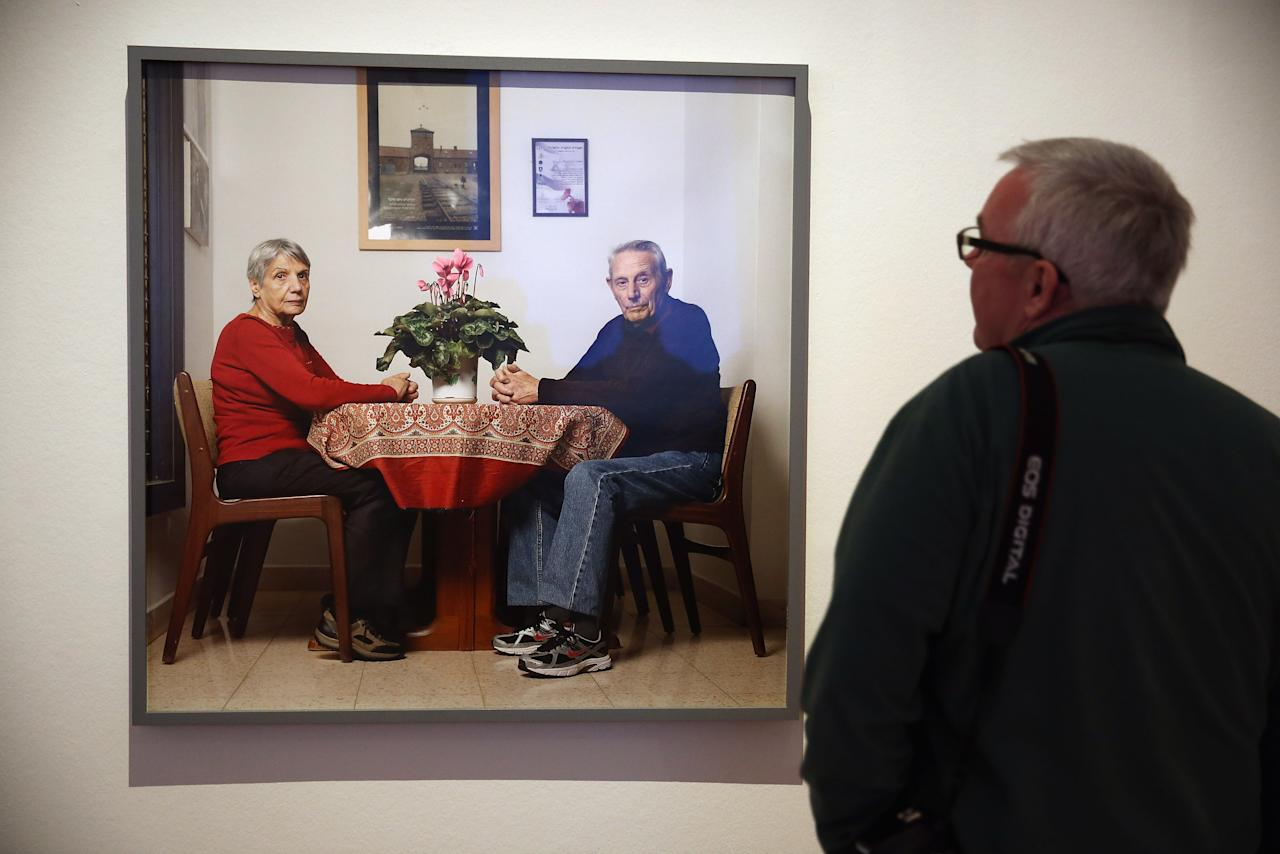 "BERLIN, GERMANY - APRIL 04:  A visitor looks at a photograph of Jews Herbert and Rina Nussan sitting at their kitchen table at the exhibition ""The Whole Truth - Everything You Always Wanted To Know About Jews . . . "" at the Juedisches Museum (Jewish Museum) on April 4, 2013 in Berlin, Germany. The exhibition presents every-day aspects of Jewish life, poses simple questions answered with exhibits and challenges certain stereotypes. However its live exhibit, which features a Jewish person who sits in a plastic enclosure open on one side for several hours a day to answer visitors' questions, has sparked criticism from some Jewish groups.  (Photo by Sean Gallup/Getty Images)"