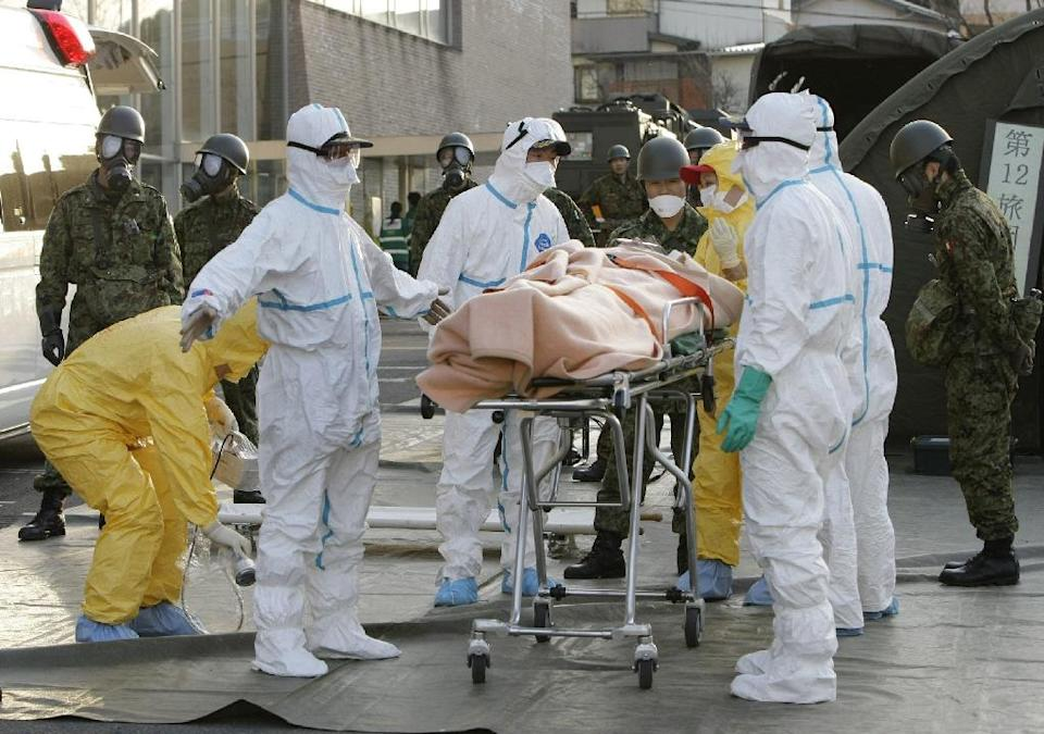 A person, believed to be have been contaminated with radiation, is wheeled to an ambulance near a treatment centre in Nihonmatsu city, Japan's Fukushima prefecture, in March 2011 (AFP Photo/-)