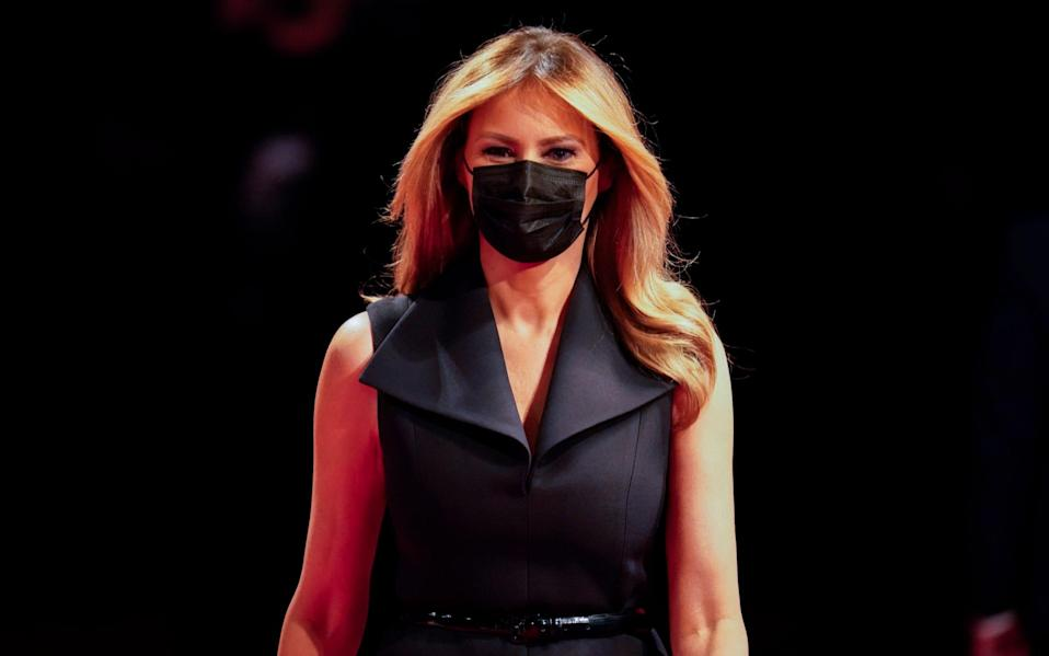 Melania Trump wears a tuxedo dress with a matching mask - AP