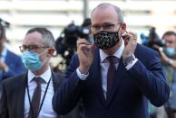 Irish Foreign Minister Simon Coveney puts on his face mask after speaking to the media, in Brussels