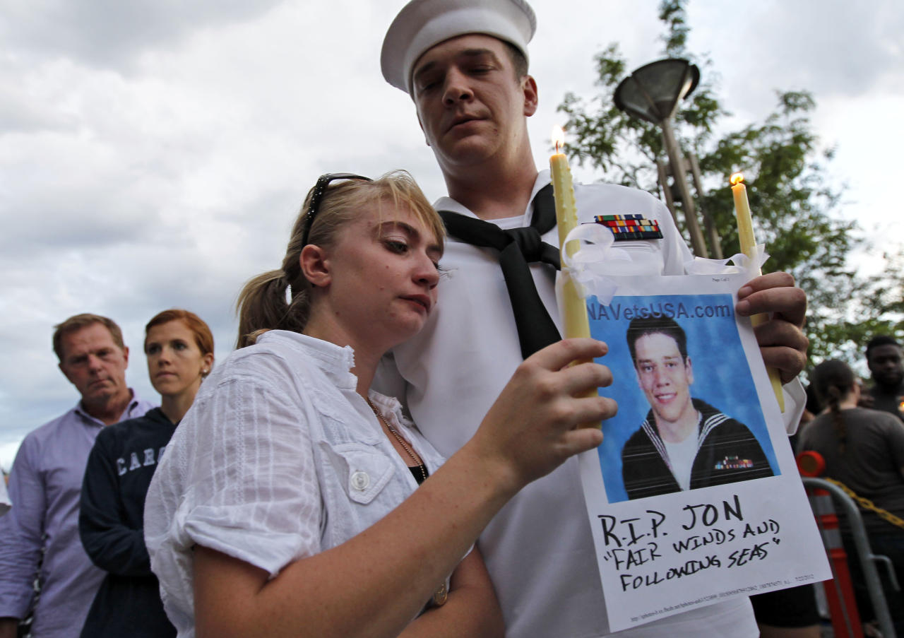 "U.S. Navy Petty Officer Second Class Keith Hoover, right, with his girlfriend Monica Matryba hold a photo of fellow sailor Jon Larimer at the Aurora Municipal Center, Sunday, July 22, 2012, in Aurora, Colo., during a prayer vigil for the victims of Friday's mass shooting at a movie theater. Twelve people were killed and dozens were injured in a shooting attack early Friday at the packed theater during a showing of the Batman movie, ""The Dark Knight Rises."" Police have identified the suspected shooter as James Holmes, 24. (AP Photo/Alex Brandon)"