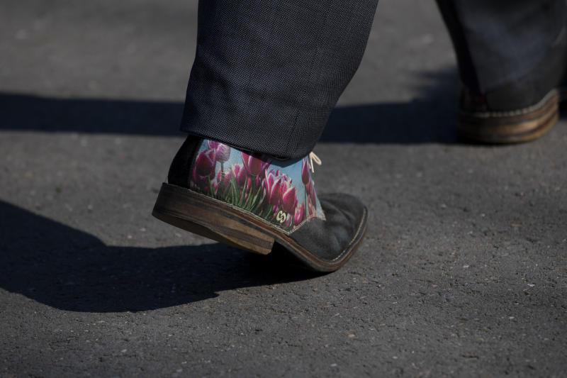 The shoes of Bart Siemerink, director of the world-renowned Dutch flower garden Keukenhof, are adorned with a design of tulips, as he walks the empty lanes of the garden in Lisse, Netherlands, Thursday, March 26, 2020. Keukenhof, which attracted 1.5 million visitors last year, will not open this year after the Dutch government extended its ban on gatherings to June 1 in an attempt to slow the spread of the coronavirus. Instead of opening, it will allow people to virtually visit its colorful floral displays through its social media and online channels. The new coronavirus causes mild or moderate symptoms for most people, but for some, especially older adults and people with existing health problems, it can cause more severe illness or death. (AP Photo/Peter Dejong)