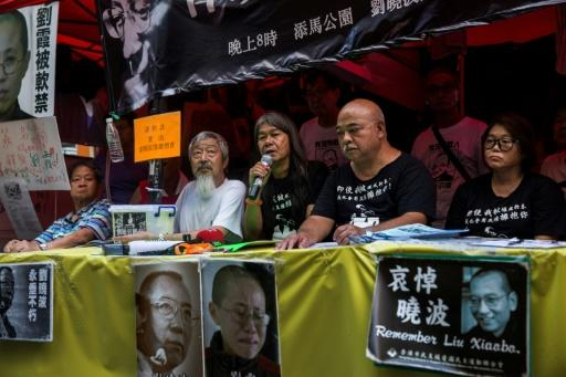 Veteran activist Leung Kwok-hung, also known as Long Hair, (C), speaks as pro-democracy campaigners Tuesday celebrate the release of the widow of Chinese Nobel dissident Liu Xiaobo