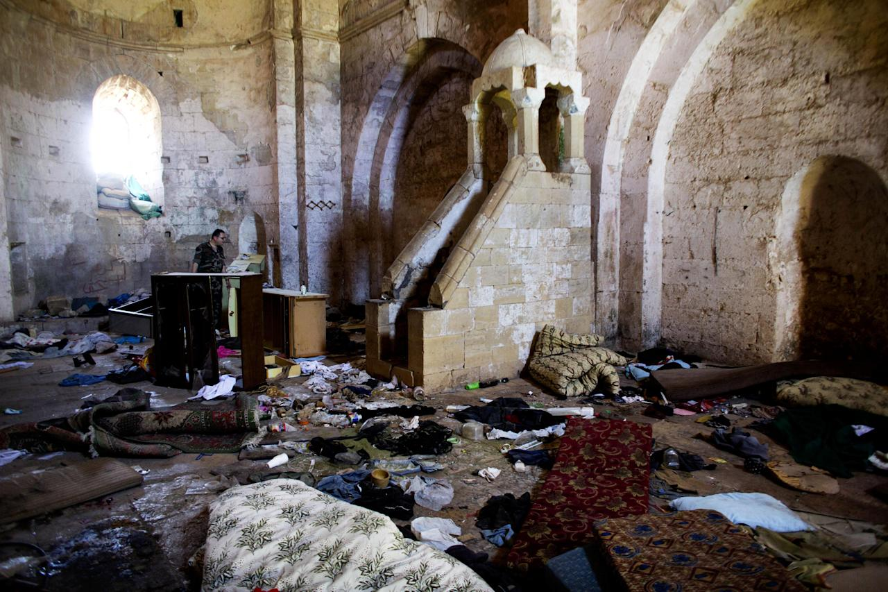 This photo made on Thursday, May 1, 2014, shows belongings of Syrian rebels inside a chapel at Crac des Chevaliers, the world's best preserved medieval Crusader castle, in Syria. The village was destroyed in fighting between the government and rebel forces while the castle, listed as a UNESCO world heritage site, also has been damaged over the past two years. (AP Photo/Dusan Vranic)