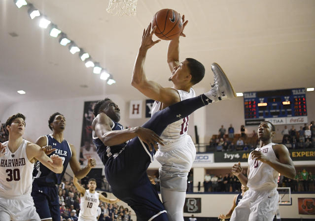 Yale's Miye Oni, left, fouls Harvard's Bryce Aiken as he shoots during the second half of an NCAA college basketball game for the Ivy League championship at Yale University in New Haven, Conn., Sunday, March 17, 2019, in New Haven, Conn. (AP Photo/Jessica Hill)
