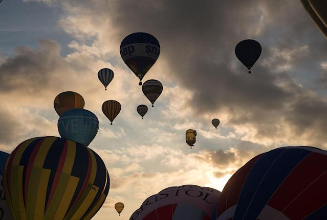 <p>Hot air balloons are inflated and take to the skies as they participate in the mass assent at sunrise in the main arena on the second day of the Bristol International Balloon Fiesta on August 11, 2017 in Bristol, England. (Photo: Matt Cardy/Getty Images) </p>